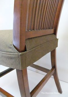Seat cover for dining chair. Clean, simple wrap around design that fits snugly around legs with velcro. This would be simple to make by altering this DIY: www.athomeontheba...