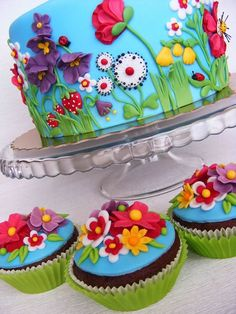 This is the brightest color palette of a fondant covered cake I've seen. Absolutely gorgeous for Spring with bright flowers & even lady bugs & then to serve the matching chocolate cupcakes is an awesome Birthday centerpiece.