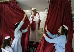 In the compound chapel, disciples shut the curtains in front of INRI Cristo after he has delivered the sermon of the day. Brazil, 2014.