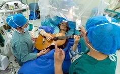 A patient plays the guitar while undergoing brain surgery at a hospital in Shenzhen city, south China's Guangdong province. The 57-year-old patient is the first in China and the seventh in the world to receive 'deep brain stimulation' (DBS), a surgical procedure in which two thin, insulated electrodes are inserted into the brain to block the signals that cause the symptoms of dystonia.