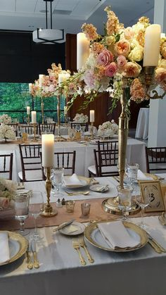 Candelabra centerpieces combine with compote arrangements and gilded candlelight along the center of banquet tables