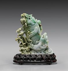 """CARVED JADEITE GROUP: Dragon-fish 翡翠雕龍魚組擺件 Finely carved, Chinese jadeite group; of two dragon-fish surging out of the swirling waves, with a pearl and a small chilong off to one side; the jadeite attractively multi-colored with areas of translucent bright apple green, and with russet rivering; H: 6 1/2""""; matching wave-form wood stand"""