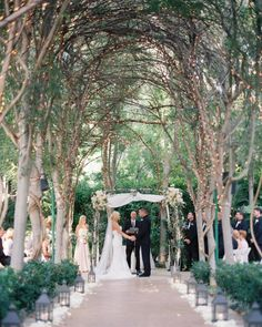 We seriously can't get over how romantic this ceremony setup is! A canopy of Christmas lights and a petal-lined aisle? Yes, please! | Photography + Cinematography: @nataliebrayphoto | Floral Design: @casicieloweddings
