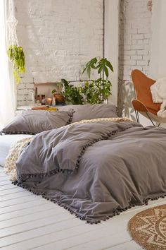 Grey pom-fringe duvet cover + retro leather chair + green ferns in a white room = the bohemian haven