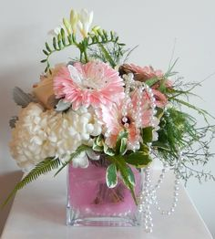 A beautiful arrangement for a new Baby Girl from Dizennio Floral Boutique-Vaughan. Ivory hydrangea with light greens, white freesia and pale pink gerbera with pearls and pink tule in the vase