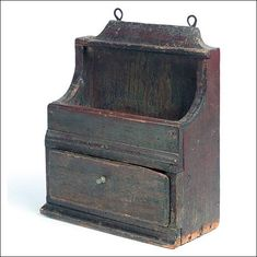 """GOOD EARLY HANGING BOX. New England, 18th century, pine. Spoon rack over well over a single dovetailed drawer. Appears untouched, retaining old, dry, grungy paint. Expected wear and minor losses. 16 1/2""""h. 13 3/4""""w. 6 1/4""""d. Illustrated in Kettell, Early Pine Furniture of New England, frontispiece. Sold at Garth's Auction 3/26/27/2010."""