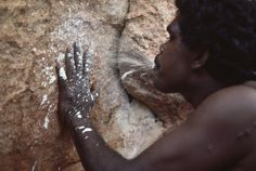 An Aborigine sprays paint on his hand as a symbol he is part of the tribe, in Nat Geo video about Gagudju of Australia.