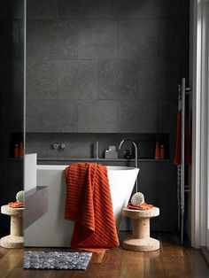 i too Love the dark grey tiles on the wall, white bath and the pop of the orange towels picking up the warm wood flooring. the pebble bath mat is fun too.
