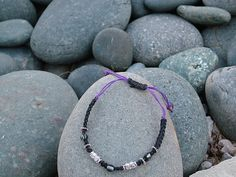 Black and purple hemp are sharp with this metal and glass bead adjustable bracelet.  More info. available at:  www.justjuliewrites.etsy.com