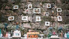 Molduras, fotos, flores e vidrinhos suavizam a parede de pedra do fundo do bolo.