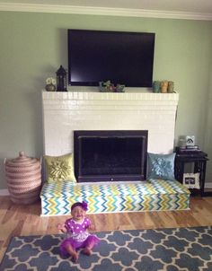 Baby proofing fireplace. DIY Fireplace bench. Cut plywood to fit and cover with memory foam and fabric!