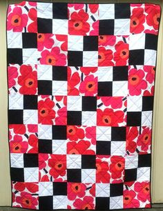 The beauty of this simple Flowers on the Checkerboard Quilt Pattern is that the design accommodates a number of larger print patterns.