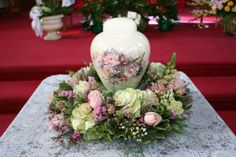 Flowers by Seasonal Celebrations. http://www.seasonalcelebrations.com A flower wreath to surround a cremation urn. Notice how the flowers in the wreath coordinate with the flowers on the urn.