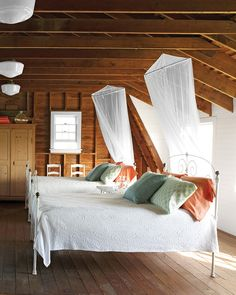 "The upstairs ""dormitory"" evokes childhood summers, with vintage schoolhouse lights, mosquito netting, and cast-iron beds. White dormers contrast with the original woodwork, which Cox oiled but left unpainted. Light-colored bedding gives the room its relaxing air. Cox says her 95-year-old father, Sil, prefers the barn to the main house for his naps."