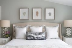 Beautiful attic bedroom features sloped ceiling over a trio of art placed over a camel colored nailhead headboard on bed dressed in black and white shams flanked by white Greek key nightstands, Worlds Away Pagoda White Nightstands, topped with mercury glass lamps.