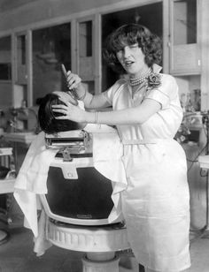 The first licensed female hair stylist in New York City, Miss Jeanne Devereux, is photographed shaving a customer .