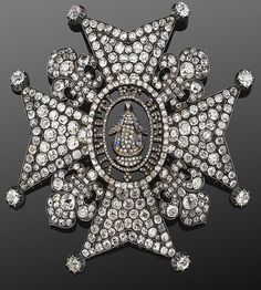An antique old mine cut diamond Maltese Cross brooch, circa 1850s. Old mine cut diamonds set in a Maltese cross with fleur de lys accents surrounding an image of the Virgin Mary with a sapphire robe, mounted on rock crystal with the Latin motto 'Virtue and Merit'.