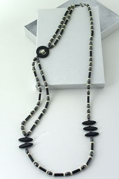 Asymmetrical long necklace made from black agate disks and tubes, hematite beads and off-white flat wood rondelles