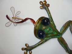 Huge copper and brass frog with glass eyes measures 4' long. He's made to go outdoors and can mount on a wall or lay in one of your flower beds. A tasty dragon-fly is right on the tip of his tongue.