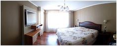 Panel lacado en dormitorio con repisas enchapadas en madera natural.