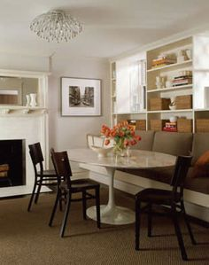 Like the basic concept of this design--the oblong Saarinen table, wood chairs, and shelving. Especially like the fireplace in the dining room. Saarinen Tisch, Saarinen Table, Kitchen Banquette, Banquette Seating, Tulip Table, Oval Table, Table And Chairs, Wood Chairs, Living Room Sofa