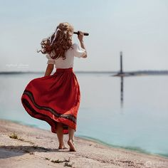 Nice effect of angles with use of woman's body, hand telescope, and light house with blown skirt for added effect, great picture