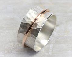 Ein goldener Ring aus **585 Rotgold** umkreist den strukturierten breiten Bandring aus **925 Silber**. Der äußere polierte Goldring lässt sich drehen und verschieben. Durch die Hohlkehlenform...