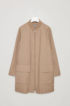 Made from crisp waxed cotton, this long coat has a ribbed neckline and a soft cotton lining. A lightweight style, it is an easy A-line shape with raglan sleeves, large front pockets and a metal zip fastening.