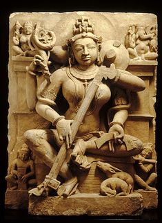 """Saraswati — 10th century, sandstone. This sculpture once stood in a niche in a Hindu temple. Saraswati is a goddess who embodies the power of speech, of music (she is playing the stringed instrument known as the """"vina""""), and of learning (she holds a manuscript in her lower left hand)."""