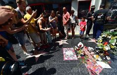 米カリフォルニア(California)州ハリウッド(Hollywood)のハリウッド大通り(Hollywood Boulevard)にある故マイケル・ジャクソン(Michael Jackson)さんの名前が刻まれた星形プレートの周辺に飾られた花や縫いぐるみとその写真を撮る人たち(2014年6月25日撮影)。(c)AFP/Frederic J. BROWN ▼26Jun2014AFP|M・ジャクソンさん没後5年、ファンが墓前で追悼 http://www.afpbb.com/articles/-/3018827