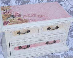 This is a beautiful vintage jewelry box hand painted in retro chic aqua with gold accents.  The top is decoupaged in complimentary paper and the three slide out drawers are also lined with matching paper.  The top lid opens to 9 small storage compartments and a ring pillow.  It is 6 1/2 x 11 1/2 x 8 1/2 inches high.