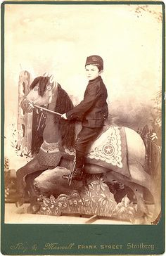 Canadian cabinet card of boy sitting astride a studio prop horse. he looks almost as fake as his cardboard steed.