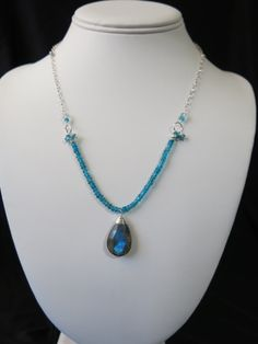 Blue Apatite and Labroadorite Necklace. Large Labradorite briolette wrapped in Sterling Silver surrounded by bright Blue Apatite. www.sarahwalkerjewlewry.com