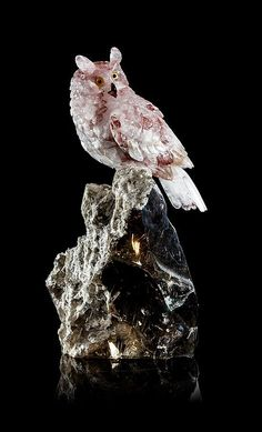 "<b>A Red Quartz Horned Owl Carving, Peter Mueller,</b> <br  /> Brazil, <br  /> convincingly depicting a watchful owl perched on a boulder, the body composed of hematite included ""red"" quartz where the red hue is present in patches giving the appearance of speckled feathers, the eyes inset with citrine and onyx accents, the transparent beak formed of garnet with a red coral tongue, the talons in gold plated silver clutching the attractive rutile included quartz crystal base which glows with…"