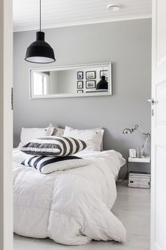 Black, white and grey bedroom with big comfy bed and black lamp