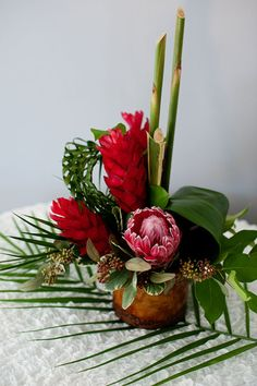 An earthy ceramic container holds this contemporary design using red ginger, tropical protea, and braided palm leafs. Tropical Wedding Centerpieces, Tropical Floral Arrangements, Beautiful Flower Arrangements, Floral Centerpieces, Beautiful Flowers, Hawaiian Flowers, Tropical Flowers, Types Of Flowers, Red Flowers