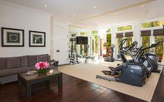 Yolanda Foster's home gym dark wood floors black and white framed prints light rug roman shades white french doors weight rack
