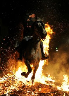 SAN BARTOLOME DE PINARES, SPAIN - JANUARY 16:  A boy covers his face from the flames as he rides a horse through a bonfire on January 16, 2011 in the small village of San Bartolome de Pinares, Spain. In honor of San Anton, the patron saint of animals, horses are riden through the bonfires on the night before the official day of honoring animals in Spain.  (Photo by Jasper Juinen/Getty Images)