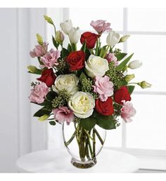 This feminine bouquet includes white and red roses, delicate pink lisianthus, elegant white tulips and seeded eucalyptus in a clear glass vase.