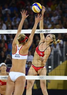 Kerri Walsh (USA red) spikes the ball past April Ross (USA white) in the women's beach volleyball gold medal match