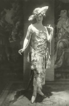 Photo, c.1919 Baron de Meyer.  Actress Elsie Ferguson wearing a printed strapless silk dress with beads, by Callot, and an ostrich feather thrust into her headband.