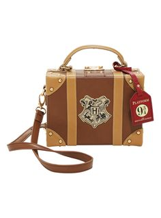 "Pack your bags and get ready to board the Hogwarts Express at Platfrom 9 3/4. This trunk style handbag is the perfect place to store your galleons, sickles and knuts. Features gold tone hardware, a Platform 9 3/4"" luggage tag and the Hogwarts crest.<div><ul><li style=""list-style-position: inside !important; list-style-type: disc !important"">Shell: 100% polyurethane</li><li style=""list-style-position: inside !important; li..."