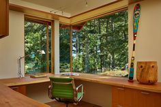In the office and many other rooms of the house, large, corner windows bring the natural surroundings inside.