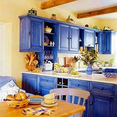 Dramatic blue kitchen cabinets against yellow painted walls.
