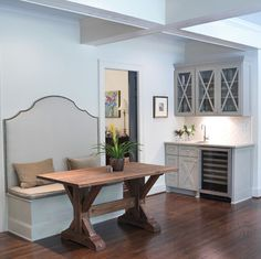 Old trestle table, banquette, and pocket door make good use of a tight space; eclectic kitchen by Clark & Zook Architects, LLC