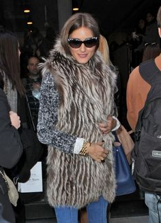 Adrienne Landau Raccoon Fur Loop vest (gilet),  flared denim trousers, sunglasses and a grey cardigan
