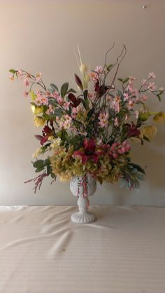 Exquisite laced container is filled with an abundance of many different flowers. Hydrangeas highlight and give it a vibrant look. Crystallized grapes, lilies, and grapevine looking leaves with grapes. Allium looking central stem. Use in a foyer or dining room chest