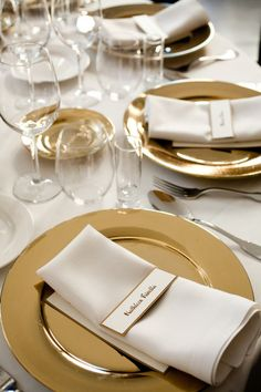 Gold chargers and coordinated place cards on classic white napkins for a an elegant, clean look