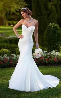The perfect balance of sophistication and simplicity, this Stella York strapless fit-and-flare wedding gown features a beautifully asymmetrical ruched bodice and skirt. You'll love how the sweetheart neckline frames your face, while the figure-flattering fitted bodice flows elegantly into a full skirt just below the hip. You can customize this dress to fit your unique style with a detachable Royal Organza Train with Satin Accent. Available at Hope's Bridal.