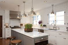 Fabulous L-shaped kitchen with perimeter cabinetry painted Dunn Edwards Droplet and kitchen island painted Dunn Edwards Legendary Gray. The kitchen features marble countertops and an incredible white subway tiled ceiling height backsplash with contrasting gray grout.